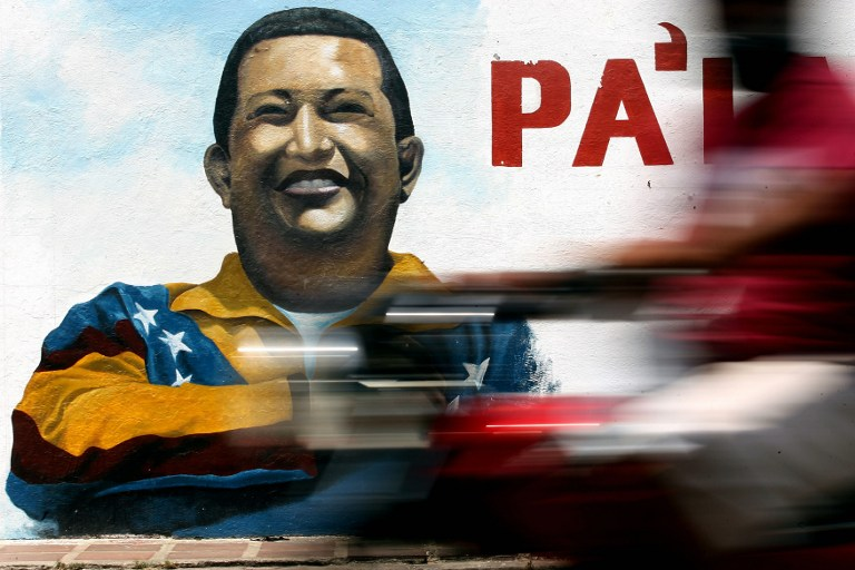 A man rides his motorbike in front of a poster of Hugo Chavez